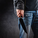 Evil man hold shiny knife, killer in action. Evil man with shiny knife - a killer person with sharp knife about to commit a homicide, murder scenery stock image