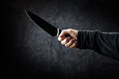 Evil man hold shiny knife, killer in action. Evil man with shiny knife - a killer person with sharp knife about to commit a homicide, murder scenery royalty free stock images