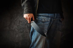 Evil man hold shiny knife, killer in action. Evil man with shiny knife - a killer person with sharp knife about to commit a homicide, murder scenery royalty free stock photography
