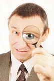 Evil man looks through a magnifying glass. Angry man looks through a magnifying glass Stock Photos