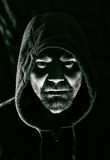 Evil man. Scary evil man with hood in darkness Royalty Free Stock Image