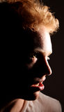 Evil man sneering. A redhaired, young man sneering into hard light Stock Photo