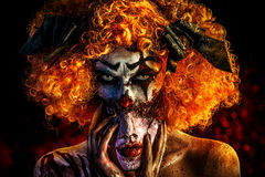 Evil mask. Close-up portrait of a terrible bloody clown with a mask. Halloween. Horror royalty free stock photos