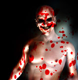 Evil On My Mind. An evil psychotic clown covered in blood Stock Images