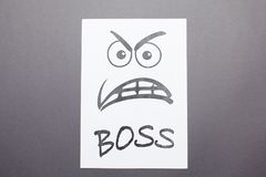 Funny picture on white paper, angry boss face. Evil painted boss face on a white paper isolated on gray background Stock Photos