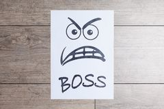 Funny picture on white paper, angry boss face. Evil painted boss face on a white paper on wood background Royalty Free Stock Photo