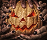 Evil pumpkin with glowing eyes that are holding. Closeup Royalty Free Stock Images