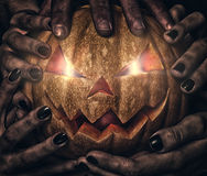 Evil pumpkin with glowing eyes that are holding Royalty Free Stock Photography