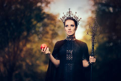 Evil Queen with Poisoned Apple in Fantasy Portrait. Beautiful dark princess using black magic spell stock photo