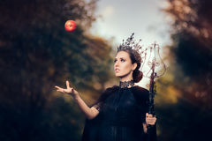 Evil Queen with Poisoned Apple in Fantasy Portrait. Beautiful dark princess using black magic spell stock images
