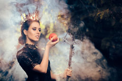 Evil Queen with Poisoned  Apple in Misty Forest. Beautiful dark princess using black magic spell Stock Image