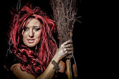 Evil red-haired witch and her broomstick Royalty Free Stock Photo