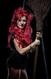 Evil red-haired witch and her broomstick Royalty Free Stock Photos