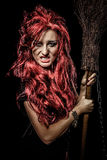 Evil red-haired witch and her broomstick Stock Image