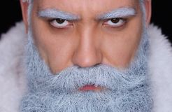 Evil Santa Claus angrily looks at the camera. On a dark background royalty free stock photography