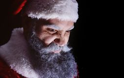 Evil Santa Claus grimaces and scares a terrible face. On a dark background stock photography