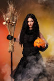 Evil but sexy witch. Halloween witch with a broom and carved pumpkin over color background with smoke Royalty Free Stock Photo