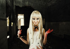 Evil smiling woman -  doll  killer. Evil smiling woman in the style of doll  killer, zombie or a ghost with a bloody hatchet in hand Royalty Free Stock Photography