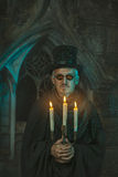Evil sorcerer with a candelabra in hand. Evil sorcerer with the chandelier in the hands of the night Stock Photography