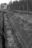 Evil Tower. Looking down the fenced border of the Dachau concentration camp Stock Photos