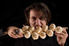 Evil vampire with scary eyes eating garlic Royalty Free Stock Image