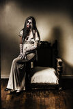 Evil vampire woman in old grunge haunted house. Evil horror photograph of a ghostly vampire woman sitting on old armchair in haunted house interior. Grunge Stock Photos