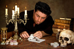 Evil voodoo. Halloween scene of a man sticking needles in a voodoo doll Stock Photos