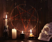 07_Evil świeczki przeciw drewnianemu tłu z pentagramem Obrazy Royalty Free
