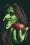 Evil witch holding a red apple Stock Photography