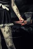 Evil woman holding a bloody ax Stock Photos
