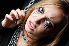 Evil zombie girl with black tears and cut throat hangs on chain. At black background Royalty Free Stock Images