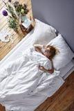 Evitando la donna del sole di mattina a letto Fotografia Stock Libera da Diritti