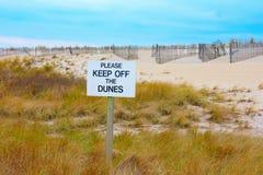 EVITE POR FAVOR LAS DUNAS firman con las dunas hermosas y el fondo del cielo azul foto de archivo libre de regalías