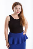 Evoke young woman in blue skirt and black top, looking at camera, isolated white background Royalty Free Stock Photo