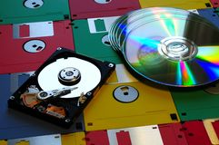 Evolution of digital storage systems. Colored Floppy Disk with modern DVD and Hard Disk Drive opened. Background Stock Photos