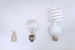 Evolution of illumination. Candle, light bulb & energy saving lamp Royalty Free Stock Photos