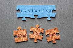 Evolution Matched and Creationism Mismatched Jigsaw. Evolution against background of human genome sequence printed on matched jigsaw pieces with Creationism Stock Photography