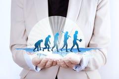 Evoluzione umana/crescita in mani della donna di affari Fotografie Stock
