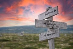evolving through adversity text engraved in wooden signpost outdoors in nature during sunset