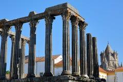 EVORA PORTUGAL: Romaren fördärvar av templet för Diana ` s och domkyrkan i bakgrunden arkivfoto