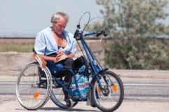 EVPATORIA, CRIMEA, UCRANIA, julio, 12,2009 - hombre mayor que lee el libro en su silla de ruedas hecha a mano en la calle Imágenes de archivo libres de regalías