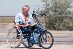 EVPATORIA, CRIMEA, UKRAINE, July,12,2009 - Senior man reading the book in his handmade wheelchair in the street royalty free stock images