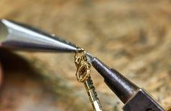 ewelry produktion Processen av att f?rbinda ett guld- l?s med ett armband med hj?lpen av tv? smyckenplatt?ng royaltyfria foton