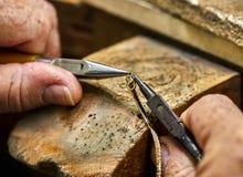 ewelry produktion Processen av att f?rbinda ett guld- l?s med ett armband med hj?lpen av tv? smyckenplatt?ng arkivbilder