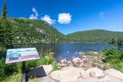 Ewidencyjny panel na małym jeziorze w Les grands parki narodowi, Quebec fotografia stock