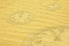 Ewigkeithintergrund - Borduhrgesichter, die im Sand sich auflösen Lizenzfreie Stockbilder
