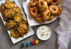 Ewish holiday Hanukkah traditional food symbols: , `Sfinj ` - Moroccan Donuts and potato latkes. Background stock image