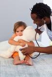 Exámenes del pediatra una niña con el estetoscopio Imagen de archivo