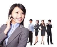 Exécutif de sourire de centre d'attention téléphonique avec des collègues Photo libre de droits