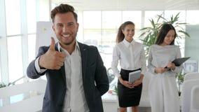 Exécutif donnant des pouces sur l'équipe d'affaires de fond dans le bureau, geste positif de plan rapproché de patron